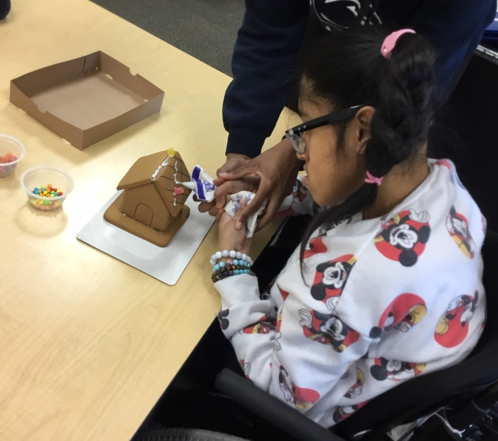 student making gingerbread house
